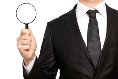 Isolated businessman in a suit holding a magnifying glass Stock Images