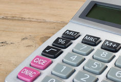 Isolated calculator in close up. Accounting concept: Close up of digital office calculator on wooden desk. Silver grey, black and pink colored  buttons Stock Images