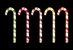 Isolated candy canes. Candy canes in five colors isolated on a black background Stock Image