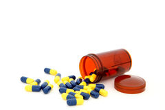 Isolated capsules spilling out from small bottle Stock Image