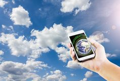Isolated cellphone or mobile with text information and earth wit. Smart phone or mobile with text information and earth with hand shadow on sky background Stock Images