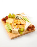 Isolated Cheeseboard. A variety of cheeses with biscuits and garnishes on a wooden cheeseboard isolated against a white background Royalty Free Stock Images