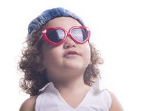 Isolated child with red sun glasses and blue hat Royalty Free Stock Image