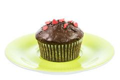 Isolated chocolate muffin on a green plate Royalty Free Stock Images
