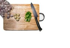 Isolated Chopped Green Onions and Peeled Garlic Cloves on a Cutting Board. stock image
