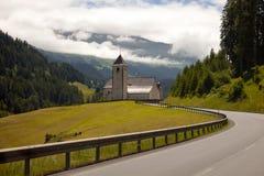 Isolated church near a mountain village in Switzerland Stock Photos