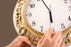 Isolated clock. Hand  in touch with a clock on a white background Royalty Free Stock Images
