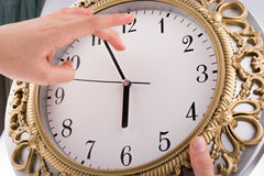 Isolated clock. Hand  in touch with a clock on a white background Stock Photo