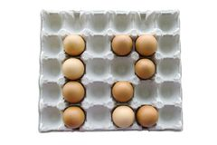 An isolated close-up of brown chicken eggs lay in a cardboard tray in the form of the number 12. Easter Concept stock images