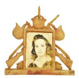 War Photo Frame With Female In Center. Isolated close up shot of a female in center of a very old War frame showing helmets, rifles, and hand grenades around the Royalty Free Stock Image