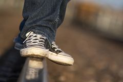 Teenager wearing retro tennis shoes balancing on rail road tracks. Isolated closeup of teenager wearing high-top tennis shoes balancing himself on railroad stock photography