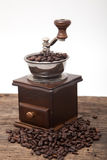 Isolated coffee bean grinder next to fresh coffe bean Royalty Free Stock Photography