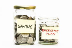 Isolated coins in jar with emergency plan and saving label. Royalty Free Stock Images