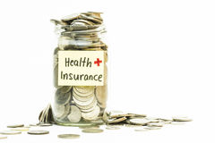 Isolated coins in jar with health insurance label Stock Photos