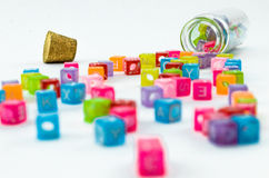 Isolated colourful small cubes with characters scattered from the vial on white background. Royalty Free Stock Photos