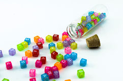 Isolated colourful small cubes with characters scattered from the vial on white background. Royalty Free Stock Images