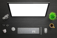 Isolated computer touch screen for mockup. Top view of black desk with camera, glasses, coffee nad plant Royalty Free Stock Photo