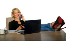Isolated corporate business portrait of young beautiful and happy woman with blonde hair smiling while working relaxed at office l. Aptop computer with feet on royalty free stock photo