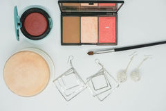 Isolated cosmetics, eye shadow brush and face powder and with earrings for women. Beauty royalty free stock photography