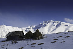 Isolated cottages in the mountains in winter. Profiled on blue sky Royalty Free Stock Photo