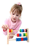 Isolated counting girl. Isolated little girl make some calculation with toy coloured wooden abacus Stock Image
