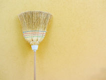 Isolated country broom on yellow background Stock Images