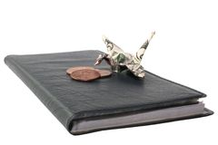 Isolated Crane with Nest Egg. Origami crane made from a $5 bill sitting on its nest with its nest egg of 3 pennies royalty free stock photo