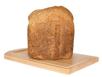 Isolated Crusty Loaf of Wholegrain Bread on Breadboard. Royalty Free Stock Photo
