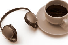 Isolated cup of coffee. With headphones, in sepia Royalty Free Stock Photo