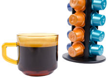 Isolated cup of coffee and coffee capsules stand Royalty Free Stock Photos
