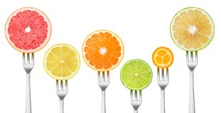 Isolated cut citrus fruits on a fork Royalty Free Stock Photos