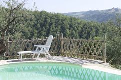 Isolated deck chair in the garden near the swimming pool - Panoramic view. Marche, Italy, Europe stock photo