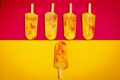 Isolated yellow-red ice cream on a colorful background. Isolated delicious yellow-red ice cream on a colorful summer background stock photos