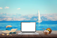 Isolated display of laptop on wooden table for mockup.  Sea, yacht and blue sky in background. Stock Photos