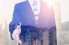 Businessman extending hand to shake with city scape. Royalty Free Stock Images