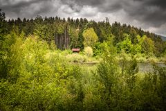 Isolated dream house beside the lake, in dramatic stormy sky and wild nature, cerknica slovenia. Isolated dream house beside the lake, in dramatic stormy sky and royalty free stock image