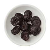 Isolated dried plums in a bowl over white background Royalty Free Stock Images