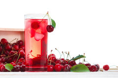 Isolated drink. Glass of cherry juice and cherries on white background. With leaves Royalty Free Stock Photography