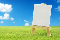 Isolated easel with empty canvas. On green grass, blue sky Royalty Free Stock Photo