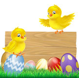 Isolated Easter Sign with Eggs and Chicks. An isolated Easter Sign with Easter eggs and cartoon yellow chicks one of which is standing on the sign Royalty Free Stock Photo