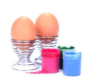 Isolated eggs and paint. Two undecorated Easter eggs in stainless steel eggcups with three paint pots isolated on white Stock Image