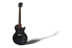 Isolated Electric Guitar. An isolated black electric guitar with lay down shadow Royalty Free Stock Photos