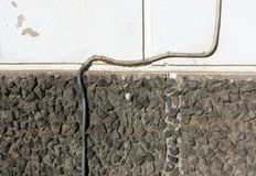 Isolated electrical wire on stone and plaster wall. Stock Photography