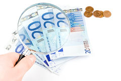 Isolated euro money under the reading glass kept i. N hand Royalty Free Stock Images
