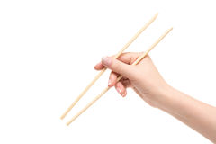 Isolated female hand holds chopsticks on a white background. Female hand holds chopsticks on a white background Stock Photography