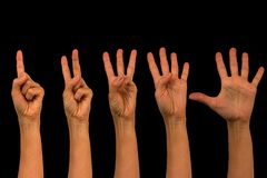 Isolated female hands on a black background. Counting on one to stock image