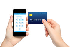 Isolated female hands holding phone and credit card and enter a. Isolated female hands holding phone and  credit card and enter a PIN code Stock Photo