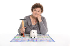 Isolated female pensioner killing her piggy bank. royalty free stock image