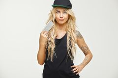 Isolated female portrait tattooed stylish blonde girl has curled her mouth and holds phone in hand with strict look. Showing skepticism or suspicion. Gloomy royalty free stock photography
