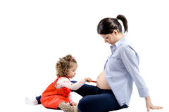 Isolated first child painting her pregnant mothers abdomen on white Royalty Free Stock Images